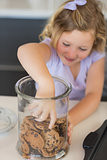 Girl reaching for cookies in jar