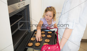 Girl with mother baking cookies