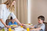 Mother serving pasta to son at dining table