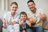 Family gesturing thumbs up on sofa