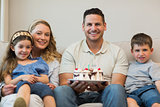 Family with cake sitting on sofa
