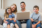 Happy family with laptop on sofa