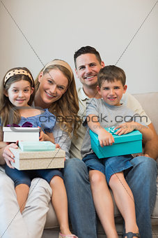 Family with presents sitting on sofa