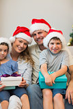 Family in Christmas hat holding presents on sofa