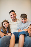 Father with son and daughter smiling on sofa
