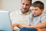 Father assisting boy in using laptop