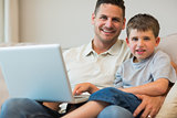 Father and boy with laptop on sofa