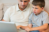 Father and son using laptop on sofa