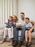 Excited family watching television on sofa