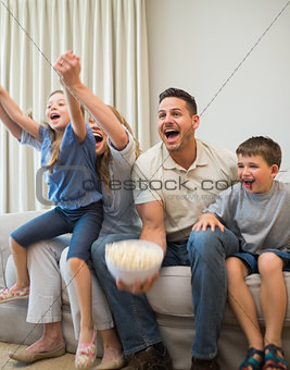 Family screaming while watching television