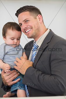 Businessman carrying baby boy at home