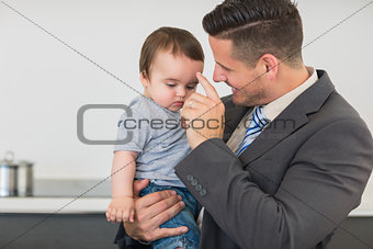 Businessman carrying baby boy in kitchen