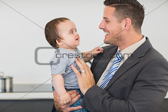 Businessman looking at baby boy in kitchen