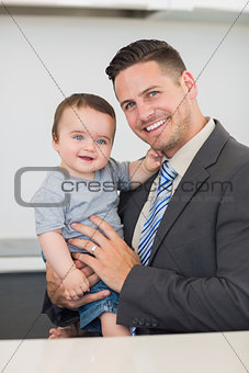 Happy businessman carrying baby boy