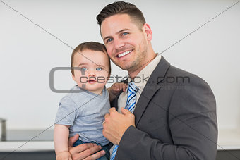 Smart businessman carrying baby boy in kitchen