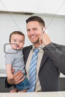 Businessman carrying baby boy while on call