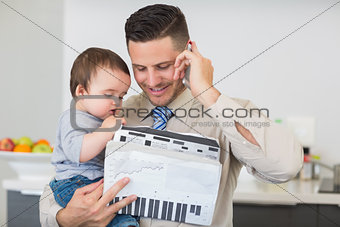 Businessman with documents carrying baby while on call