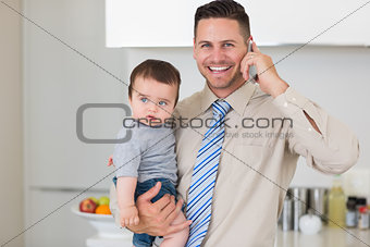 Businessman carrying baby while while using cellphone