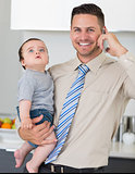 Businessman using cellphone while carrying baby in house