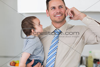 Businessman using mobile phone while carrying baby