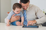 Businessman using tablet while holding baby