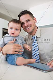 Businessman with digital tablet holding baby