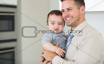Happy businessman carrying baby