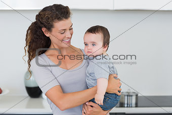 Smiling mother carrying baby
