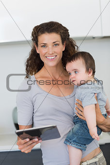 Happy mother with digital tablet carrying baby