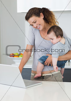 Mother using laptop while carrying baby in kitchen