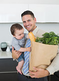 Businessman carrying groceries and baby