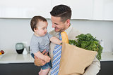 Businessman carrying baby and groceries