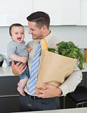 Businessman with grocery carrying baby