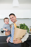 Father carrying baby boy and vegetables