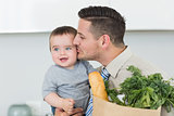 Loving businessman kissing baby boy