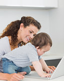 Mother looking at baby boy using laptop