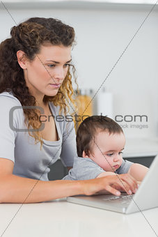 Woman with baby using laptop at counter