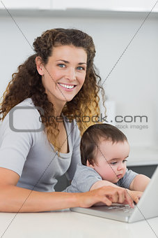 Woman with baby using laptop