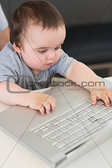 Baby using laptop at table
