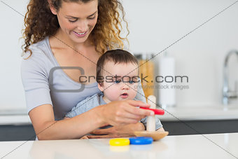 Baby boy looking at mother playing with toys