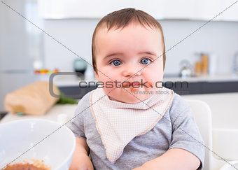 Messy baby eating food in kitchen