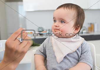 Innocent baby being fed by mother