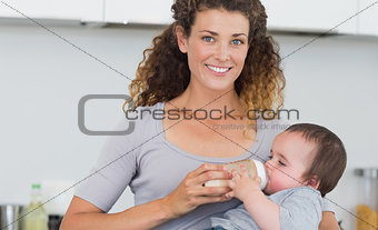 Attractive woman feeding milk to baby