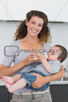 Happy mother feeding milk to baby