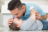 Loving father kissing baby on forehead