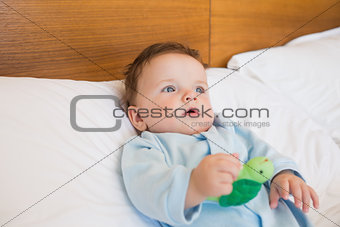 Baby holding toy in bed
