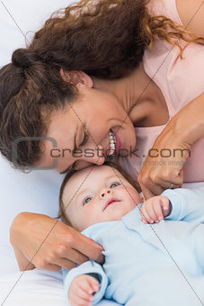 Happy mother tickling baby
