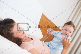 Smiling baby playing with mother