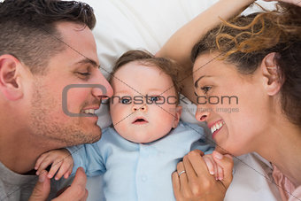 Cute baby with parents in bed