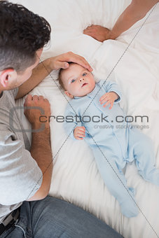 Loving father with baby on bed